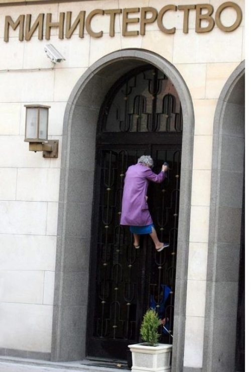 old lady climbing bank wall